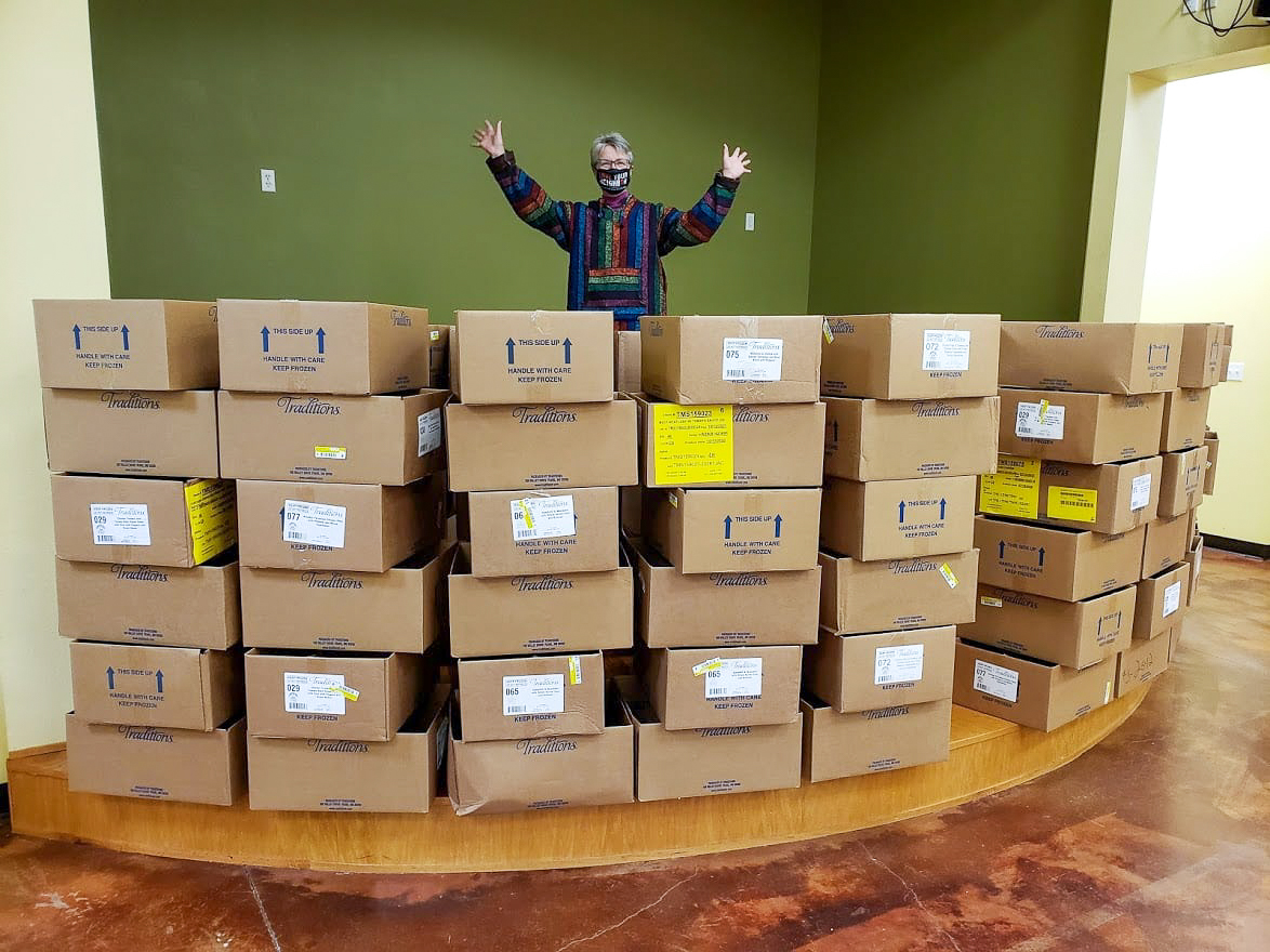volunteer with boxes of food